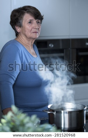 Thoughtful elderly women standing in the kitchen - stock photo
