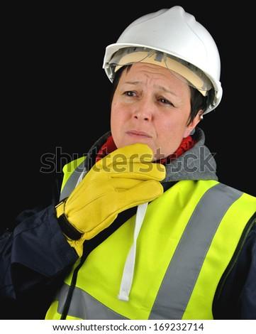 Thoughtful female builder. Isolated portrait on black background. - stock photo