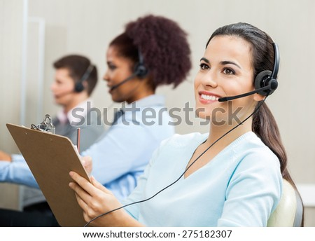 Thoughtful female customer service representative holding clipboard with colleagues in background at office