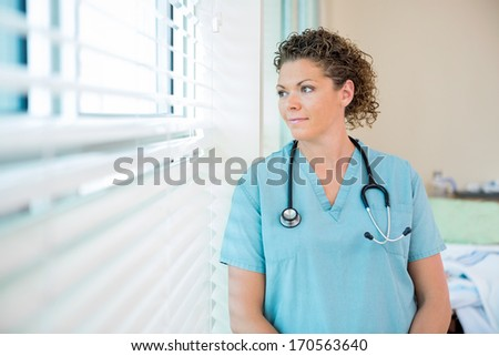 Thoughtful female nurse looking out through window in hospital room - stock photo