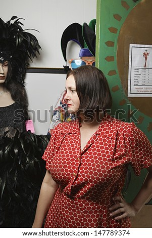Thoughtful female owner standing by costumes at the second hand store - stock photo