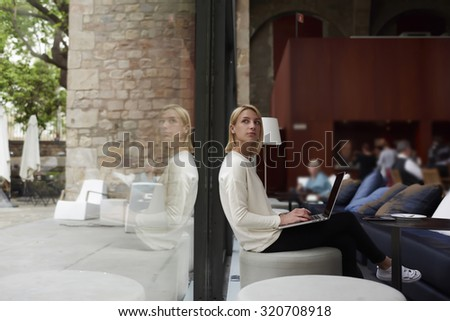 Thoughtful female person sitting in modern coffee shop interior with open laptop computer student girl doing course work on her laptop computer at the library,young businesswoman at work break working - stock photo