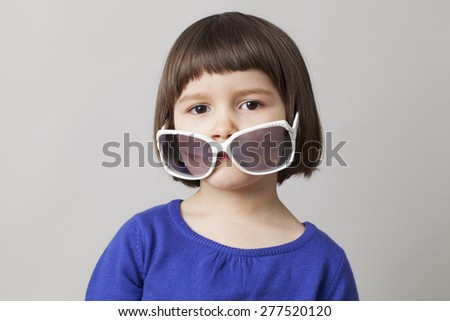 thoughtful female preschool child putting down big sunglasses for fun