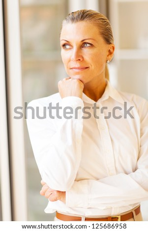 thoughtful female senior office worker looking outside window - stock photo