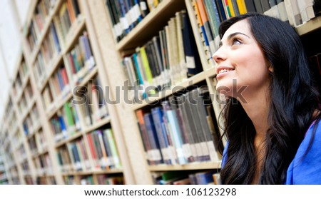 Thoughtful female student at the library loking up - stock photo