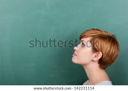 Thoughtful female student looking at a chalkboard - stock photo
