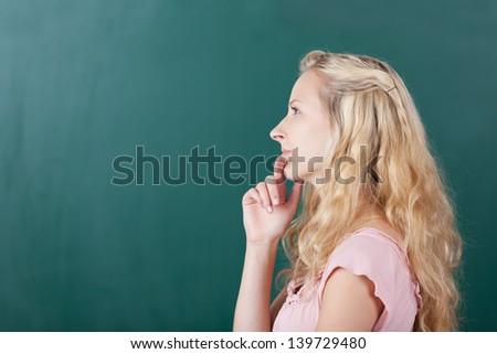 Thoughtful female teacher looking away on chalkboard - stock photo