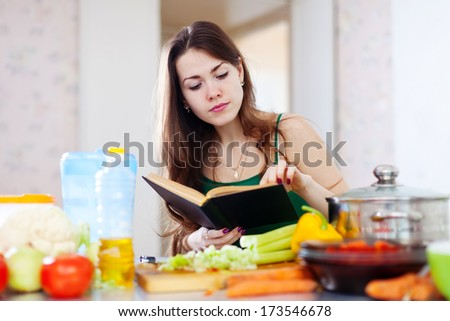 thoughtful girl cooking with cookbook in the kitchen at home - stock photo