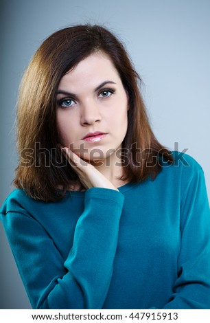 thoughtful girl in a blue t-shirt touching face hand on a gray background