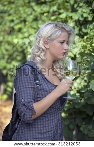 Thoughtful girl in vineyard with wineglass. Young pensive woman walking thorough vineyard with glass on white wine.