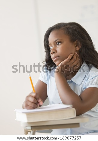 Thoughtful girl looking away while sitting with hand on chin at classroom desk