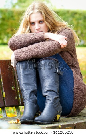 Thoughtful girl sitting on a park bench - stock photo