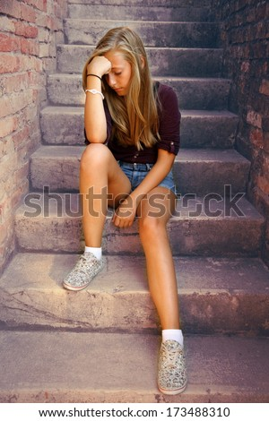 Thoughtful girl with blue eyes sitting at stone brick stairs, soft focus - stock photo