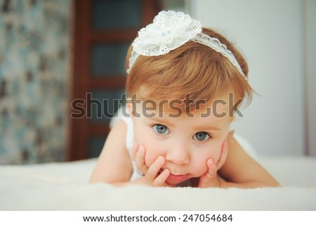 thoughtful girl with lace headband on bed - stock photo