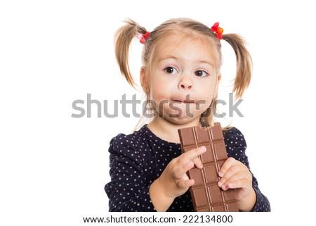 Thoughtful girl with pleasure eats chocolate. Two years. - stock photo
