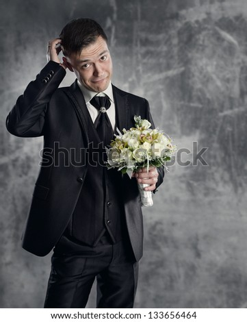 Thoughtful groom with flowers bouquet. Gray background.