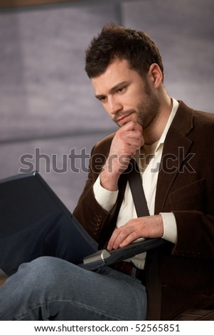 Thoughtful guy sitting with laptop computer in lap, looking serious.