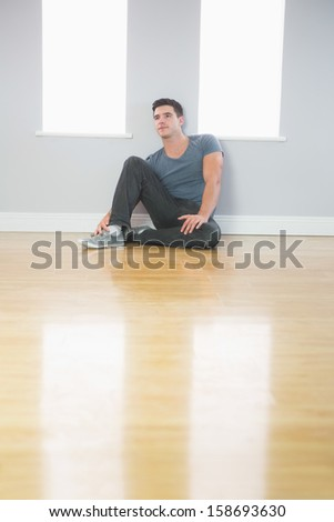 Thoughtful handsome man leaning against wall sitting on the floor in bright room