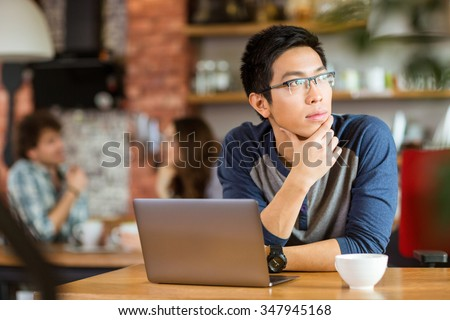 Thoughtful handsome young asian man in glasses sitting with laptop in cafe and looking away - stock photo