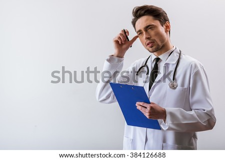 Thoughtful handsome young doctor in white gown and with stethoscope holding a folder and scratching head, on white background - stock photo