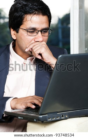 thoughtful Indian businessman working on laptop, businessman lost in deep thoughts