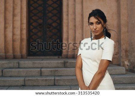thoughtful indian lady in white leather dress against ancient building. She standing in shade but lightened by reflected morning sunlight.  She stands against giant gate - stock photo