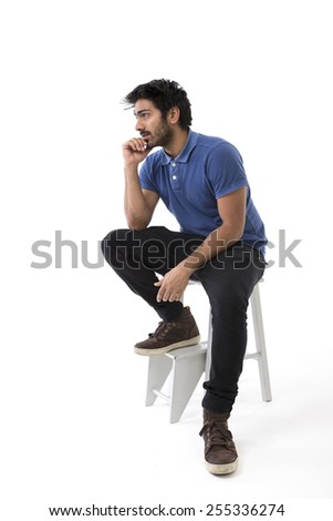 Thoughtful Indian man looking away and sitting on a chair. Isolated on white - stock photo