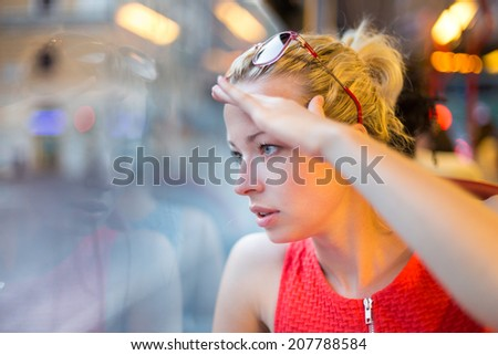 Thoughtful lady riding on a tram and looking out the window.  - stock photo