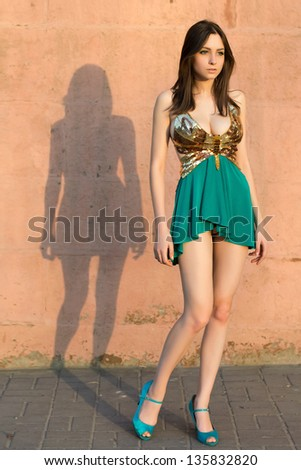 Thoughtful leggy woman posing in frank dress outdoors - stock photo