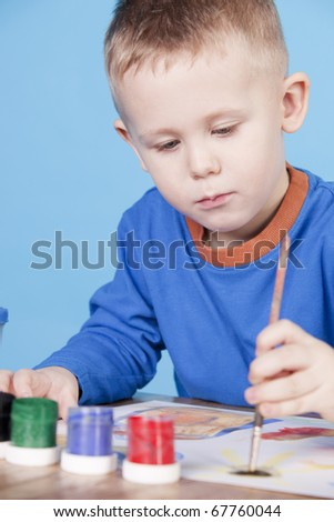 thoughtful little boy draws pictures, on blue background - stock photo