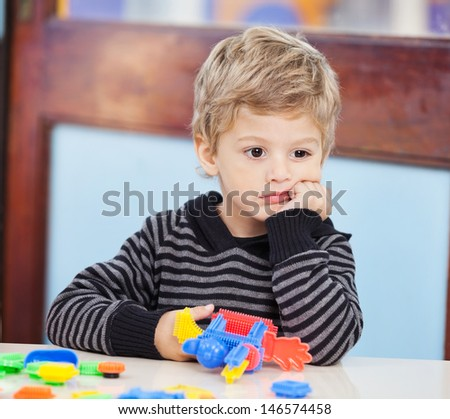 Thoughtful little boy with blocks looking away in preschool - stock photo