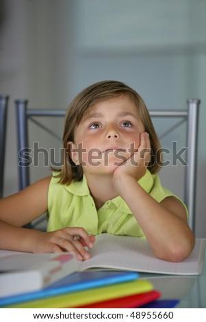 Thoughtful little girl doing homework - stock photo