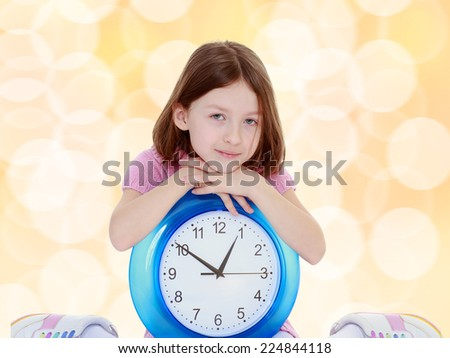 Thoughtful little girl with a big clock waiting for the new year. - stock photo