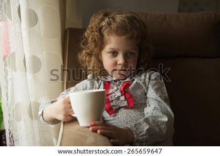 Thoughtful little girl with a mug in his hands