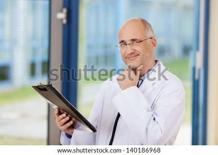 Thoughtful male doctor with hand on chin looking at camera - stock photo