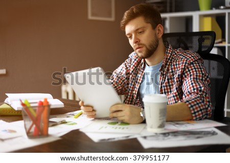 Thoughtful male person looking to the digital tablet screen while sitting in modern loft interior at the table, experienced entrepreneur reading some text or electronic book at the office