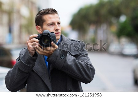 thoughtful male photographer with a camera on street - stock photo
