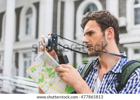 Thoughtful male tourist using camera in city
