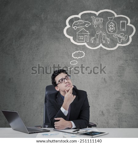 Thoughtful male worker in business suit imagine his dream on the cloud tag - stock photo