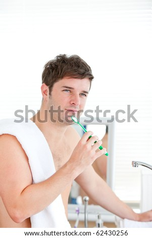 Thoughtful man brushing his tooth with towel on his shoulder in the bathroom - stock photo