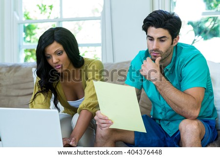 Thoughtful man checking at bills while woman using laptop at home