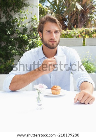 Thoughtful man having a coffee outside at the coffee shop - stock photo
