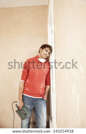 Thoughtful man holding electric sander while leaning on window frame in unrenovated house - stock photo