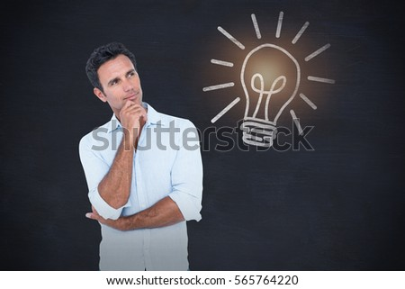 Thoughtful man in casuals with hand on chin against blackboard