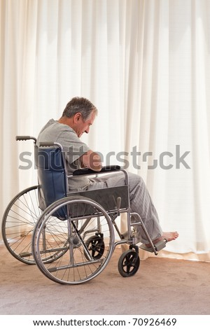 Thoughtful man in his wheelchair at home