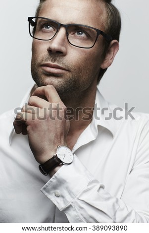 Thoughtful man in spectacles, looking up - stock photo