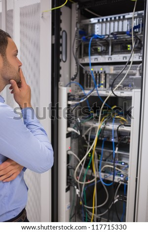 Thoughtful man looking at servers in data centre