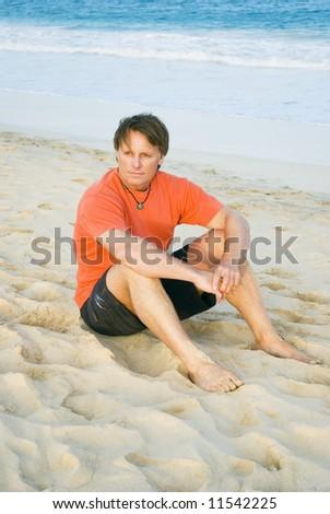 Thoughtful man on beach. - stock photo
