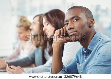 Thoughtful man sitting at desk with coworkers in office - stock photo