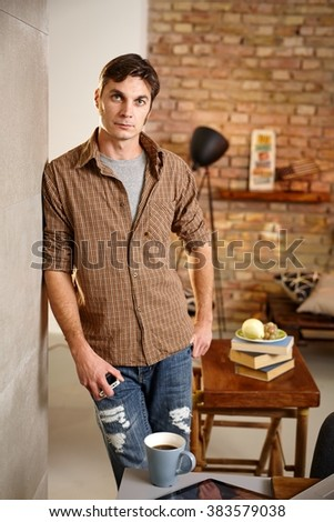Thoughtful man standing against wall at home, looking at camera. - stock photo